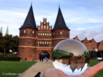 Luebeck-Holstentor-Glaskugel-in-Hand